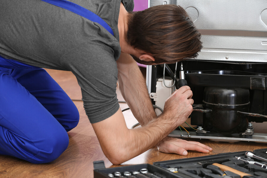 Techician on hands and knees, using a screwdriver in the back of a fridge to repair it
