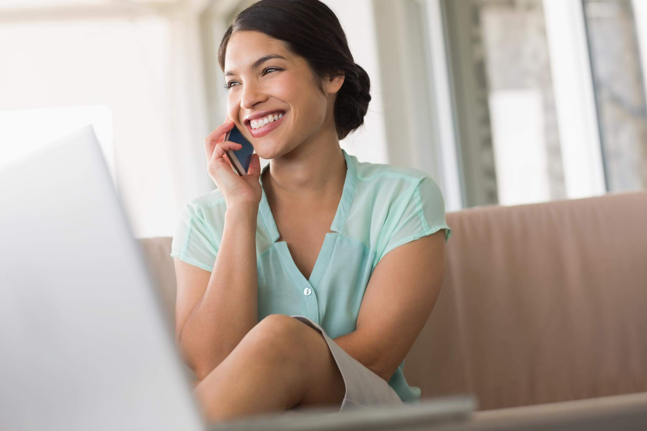 Female receptionist answering a mobile phone whilst smiling