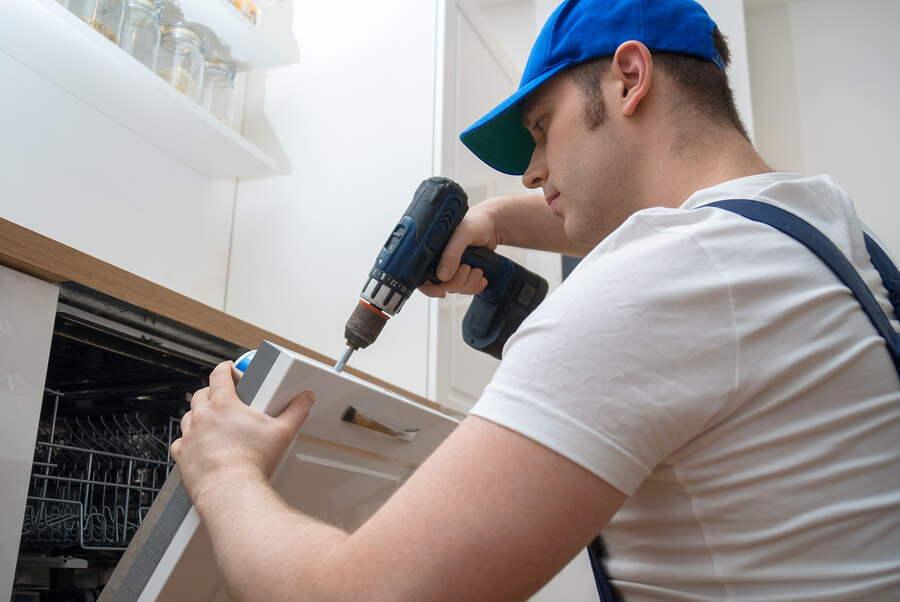 Technician with a blue cap diligently repairing a dishwasher with an electrical screwdriver