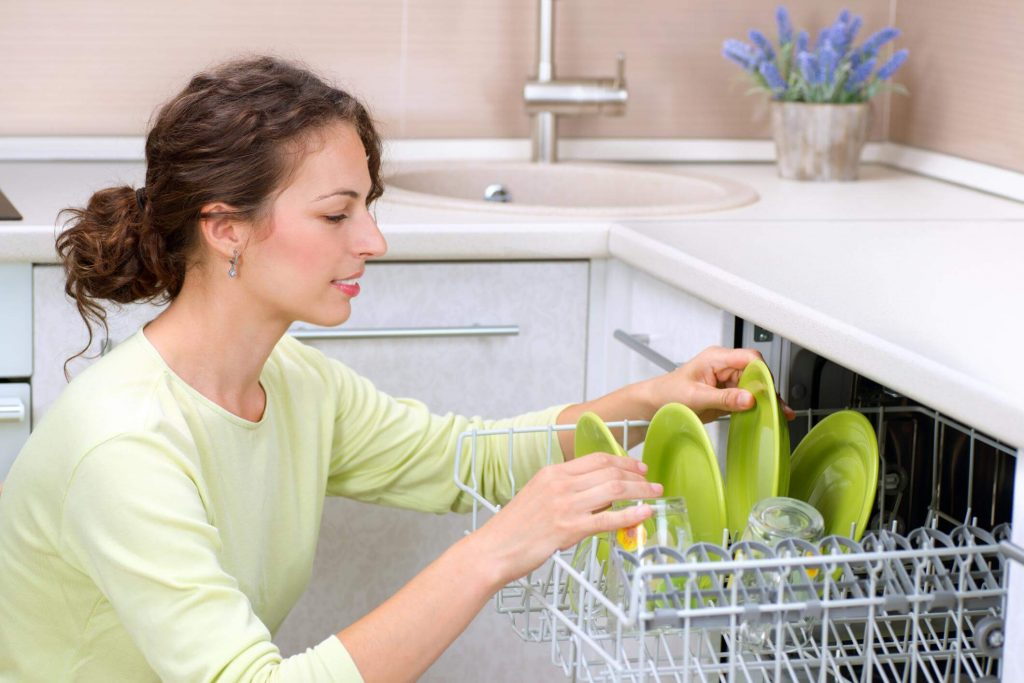 Brownhaired woman in lime-green shirt, filling up a repaired dishwasher