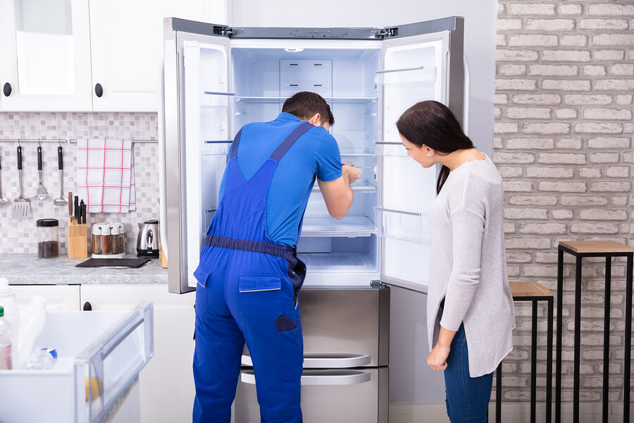 Male technician in blue coveralls repairing a build-in fridge with a screwdriver while female owner of the house watches the process