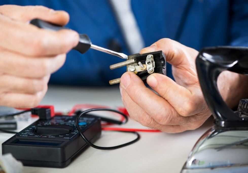 Man repairing a disassembled power plug of an applaince and repairing it with a screwdriver and a voltage meter readily available on the table.