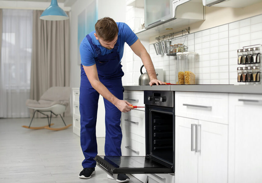 Male technician repairing an oven with a screwdriver in an off-white finished kitchen