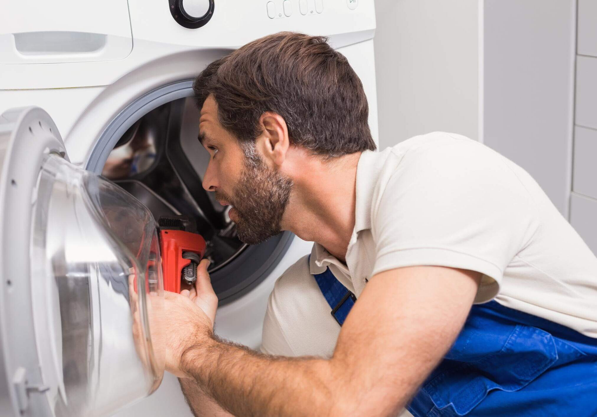 Male technician in blue coveralls and a white shirt, looking inside a washing machine whilst holding a pipe wrench