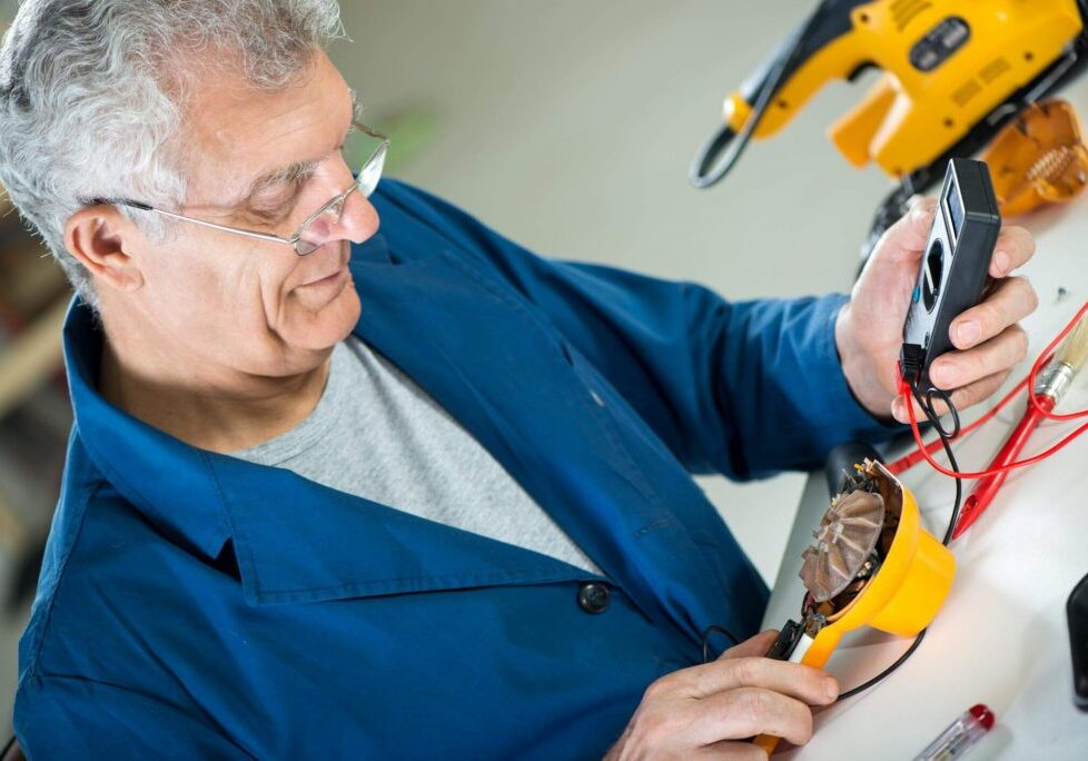 Older technician with glasses using a voltage meter to check an appliance part