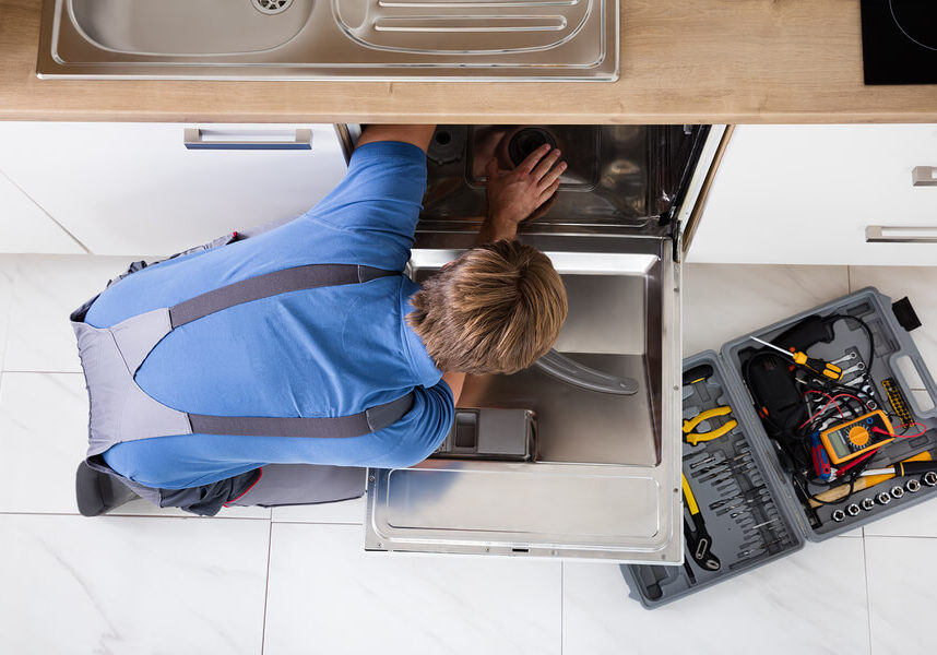 Technician fixing a dishwasher with a box full of appliance repair tools next to him