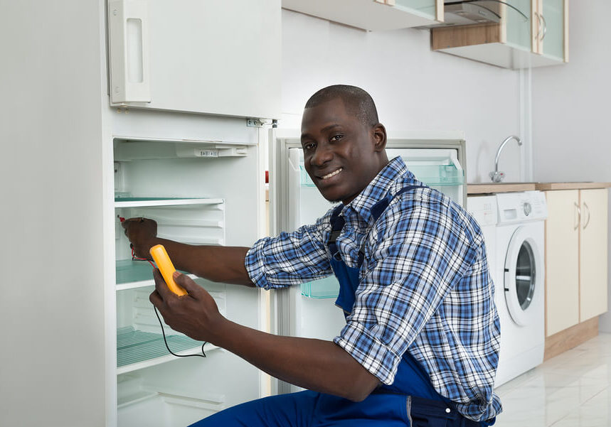 Smiling bald technician in blue coveralls using an voltage tester on a fridge