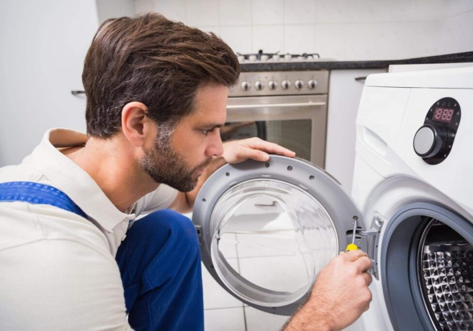 Male technician in the kitchen using a screwdriver to repair a washing machine door